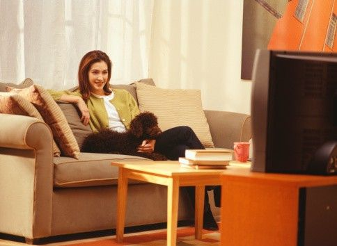 Young woman sitting on sofa with dog, watching television